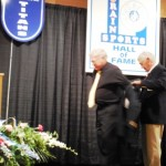 Inductee James Turton receives jacket from Ed Dohanos