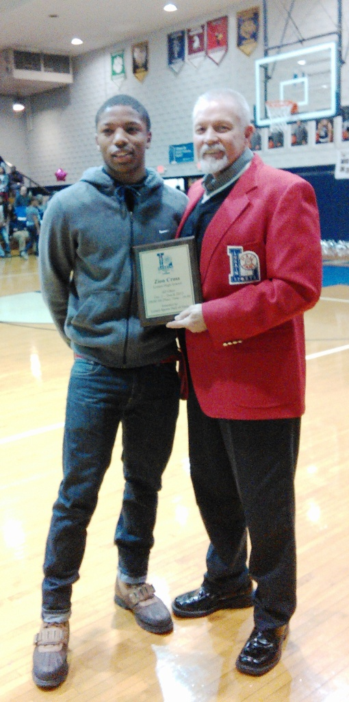 Zion Cross, at left, of Lorain High School was honored by the Lorain Sports Hall of Fame with a plaque for being named All-Ohio 5th place in the 100 meters in 2015. Making the presentation is Bill Rufo, LSHOF vice president, at the Feb. 5 Lorain-Maple Heights basketball game.