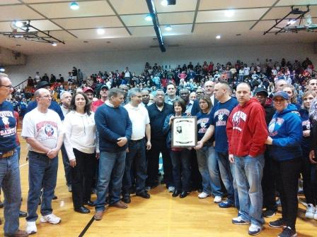 In front of a packed house, Val Stark, widow of the great Southview coach Larry Stark, holds a memorial plaque of her husband presented during a special Southview night on Feb. 19, 2016. The event coincided with the final regular season basketball game to be played in the former Southview gym. In that game, the Lorain High Titans captured their second Lake Erie League championship in a row in that game, beating Cleveland Heights 90-84 in overtime. The Lorain Sports Hall of Fame salutes the Starks, all former Southview players and coaches, and the Lorain High Titans on their back-to-back LEL titles. (Photo by Dave Simpson, LSHOF past president)