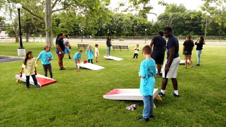 Children have fun playing cornhole beanbag toss games, with help from Lorain High football and girls volleyball players.